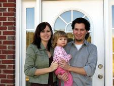 Family standing in front of a door
